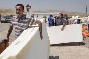 Des familles chrétiennes et yazidis ramassent des matelas à l'Eglise des Apôtres à Fishkhabour, au nord de l'Iraq, alors que Caritas vient en aide aux familles irakiennes. ©Hare Khalid / Metrography for Catholic Relief Services