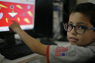 A Syrian refugee boy points at the Syrian flag he draws as he takes part in a computer classe on June 19, 2014 at Caritas Migrant Centre in Dahr El Ain, near Tripoli. Photo by Matthieu Alexandre/Caritas