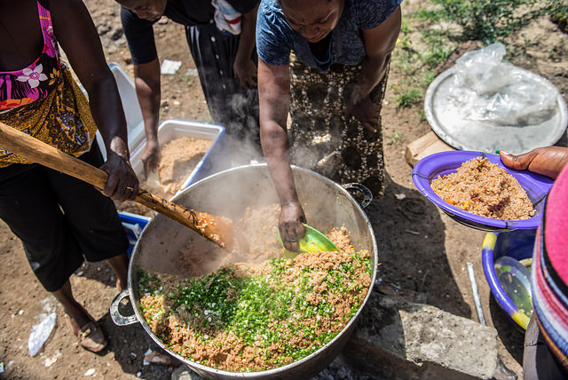 Women prepare a meal of rice and chicken for children in Allen Town. Sierra Leone. Photo by Tommy Trenchard for Caritas