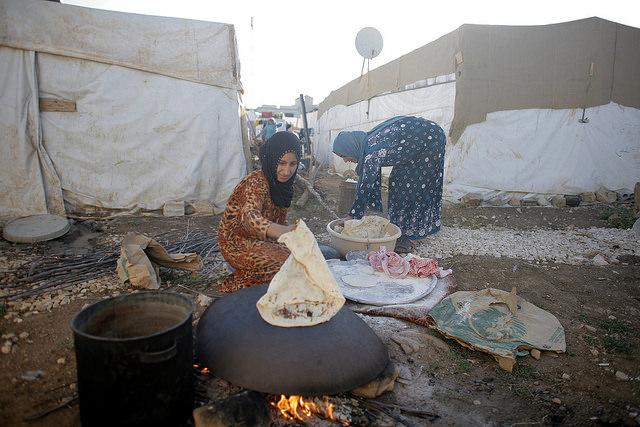 Dos mujeres cocinan en un campamento de refugiados de Siria.
