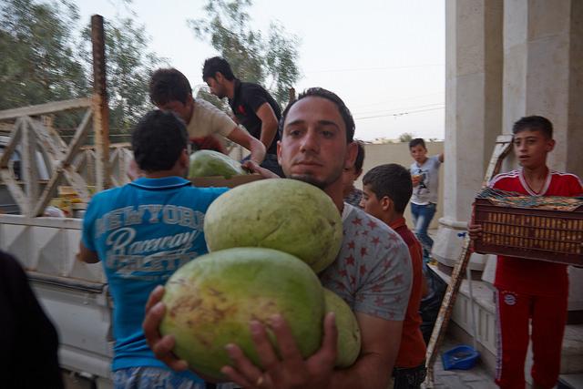 Un refugiado iraquí ayuda a descargar los alimentos a la cocina del centro de la comunidad de la iglesia de San Juan Bautista.
