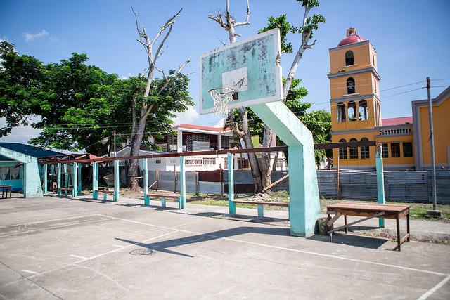 El recinto de la Academia de la Asunción estaba abarrotado de tiendas de campaña, con familias cuyas viviendas habían quedado destruidas.  Un año después, las tiendas han desaparecido y hay niños jugando por allí en lo que ahora es una cancha de baloncesto. Foto por Lukasz Cholewiak/Caritas