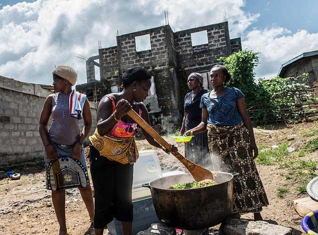 Women prepare a meal of rice and chicken for children in Allen Town. Sierra Leone.