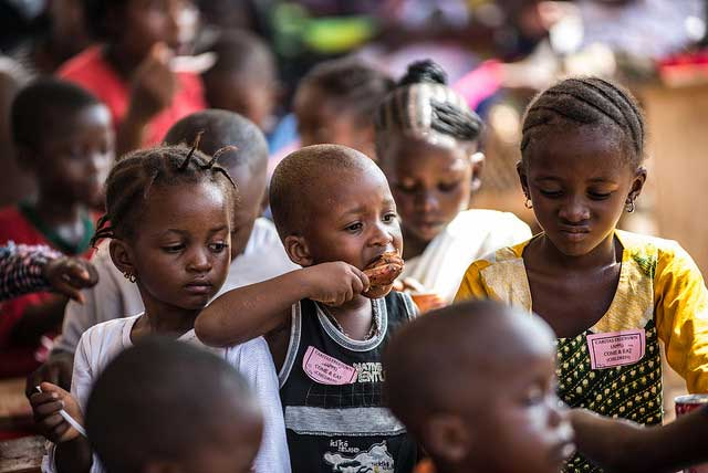 Children enjoy a meal of rice and chicken at a Caritas event in Allen Town Sierra Leone.