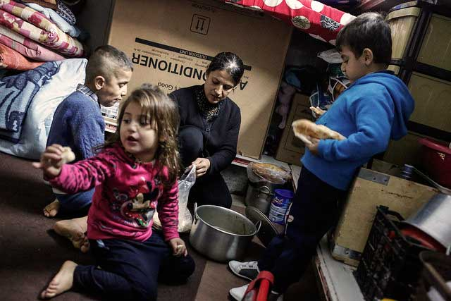 La familia de Saddam Hina Qraya comer sopa hecha de huesos hervidos en Ainkawa, Erbil, Iraq, el 3 de diciembre de 2014.