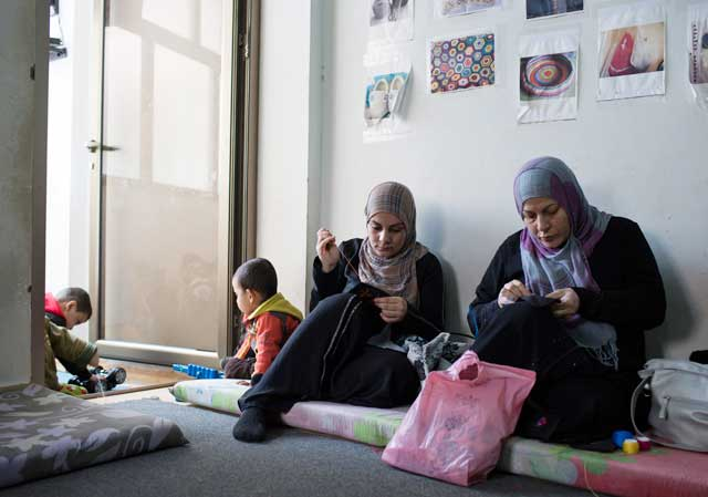 Syrian refugee women work on some cross stitching embroideries while children play