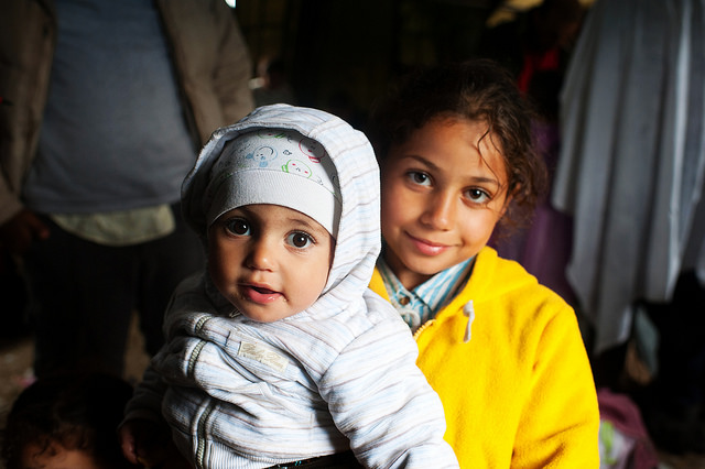 Syrian refugees Omama Basheer, 8, holds her sister, Joud, 6 months, inside a refugee aid station in the Serbian boarder town of Kanjiza. Photo by Kira Horvath for Catholic Relief Services