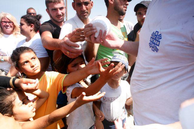 En Idomeni, al norte de Grecia, refugiados e inmigrantes se están congregando para recibir la distribución de alimentos mientras esperan a cruzar la frontera entre Grecia y Macedonia.  Matthieu Alexandre/Caritas Internationalis