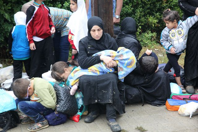 An exhausted family fleeing the conflict in the Middle East takes a rest on the road to Serbia. Arie Kievet/CORDAID