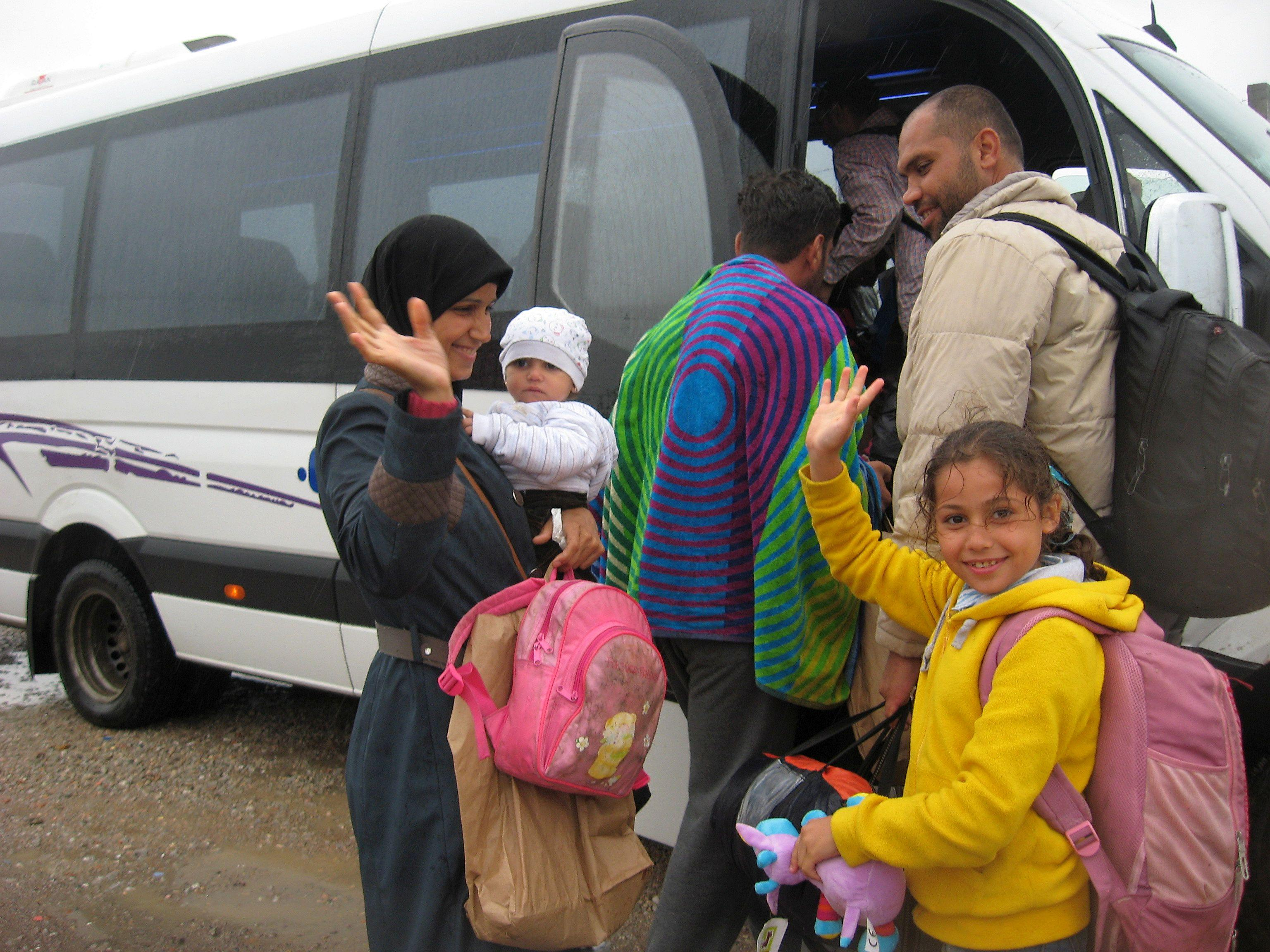 Omama (in yellow) waves goodbye as her family board a bus for Hungary. Photo by Kira Horvath for CRS