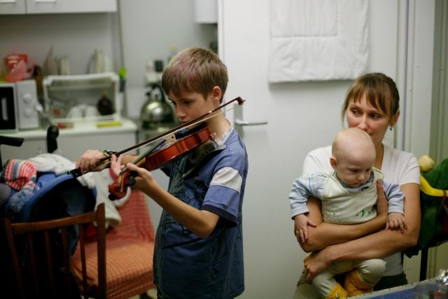 Anna Ivanova tient son nouveau-né Yurchik, pendant que son autre fils s'exerce au violon. Crédit : Matthieu Alexandre / Caritas Internationalis