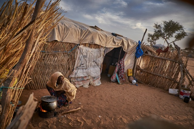 A woman cooks in a camp of displaced people in the neighbourhood of Chateau, Diffa, Niger on February 13, 2016. The camp is mixed between displaced people from Niger, Nigeria and Chad. They have fled attacks by the militant group Boko Haram on their villages and it's ongoing conflicts with the armies of each country. Caritas undertook a distribution of mosquito nets, cooking pots, sleeping covers, hygiene kits, clothes and cash transfers to the displaced. 228 households received support from Caritas among an estimated 1500 households in the vicinity of Chateau. There is still great need. There is no school system in place for the children and the housing is not adequate for many as more people arrive each day escaping hostilities. SamPhelps/Caritas