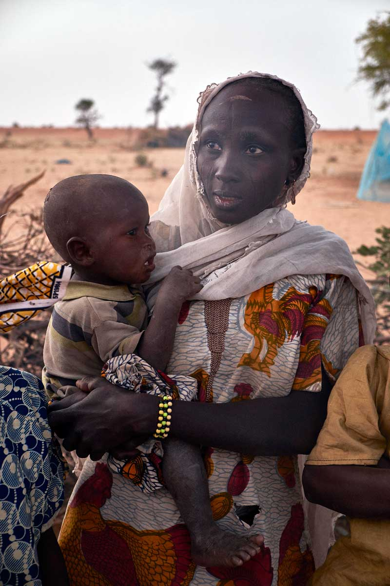 Amina Tijani holds her son at her shelter in a camp of internally displaced people by the side of the road on the highway outside of Diffa, Niger on February 11, 2015. Photo by Sam Phelps/Caritas