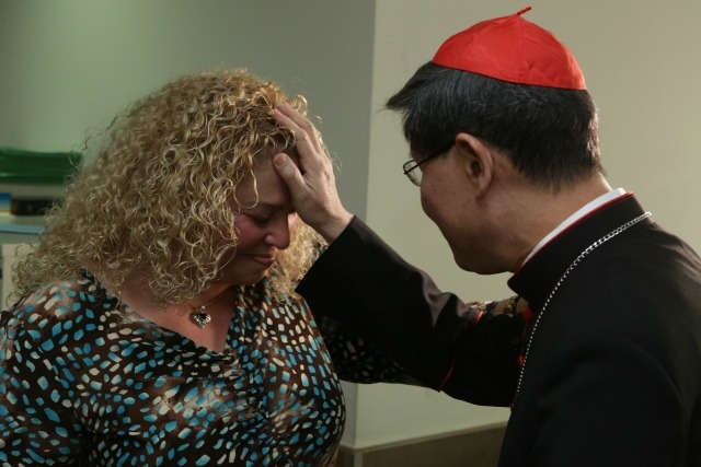 Cardinal tagle blessing a Syrian Christian refugee at a Caritas medical centre in Beirut. Credit: Caritas