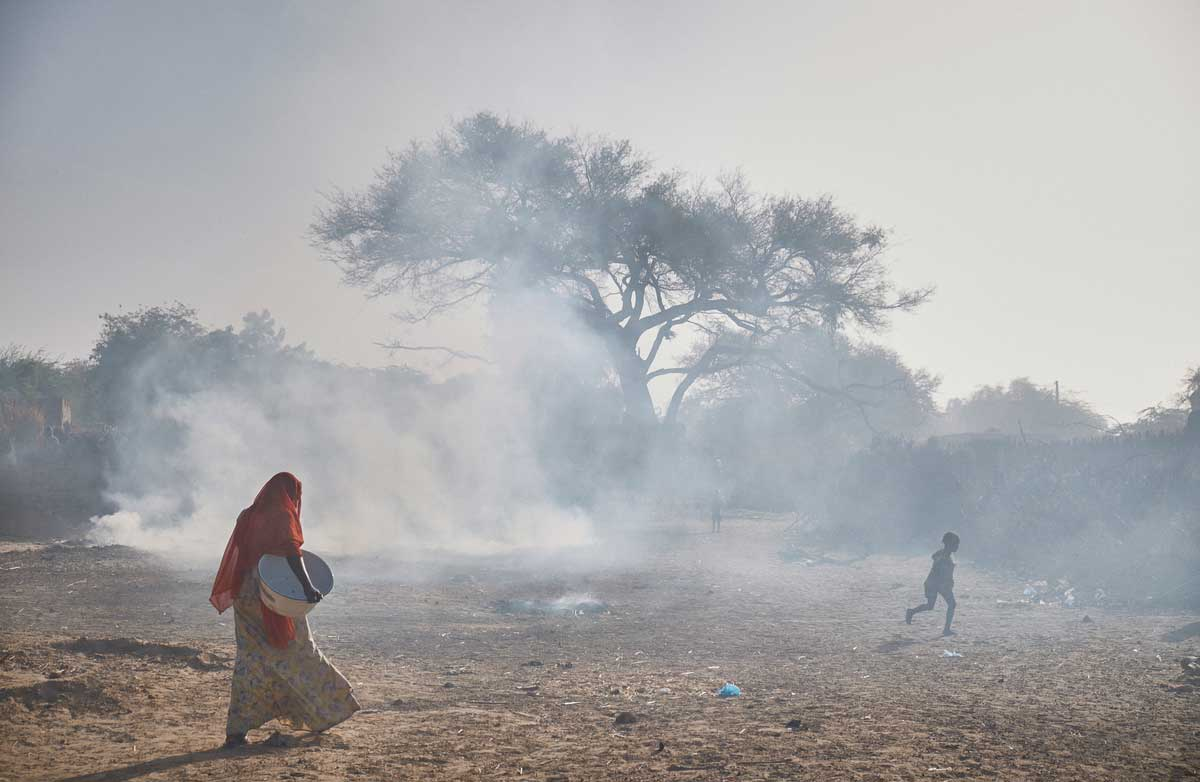A women walks through burning rubbish in the village of Boudoum near the border with Nigeria on the outskirts of Diffa, Niger on February 13, 2016. Photo by Sam Phelps/Caritas