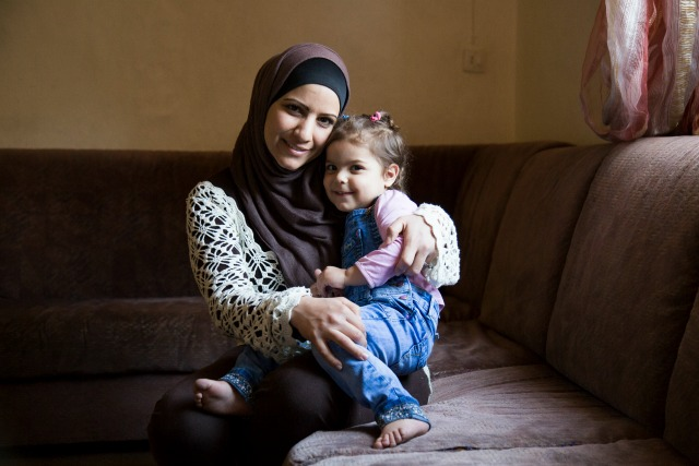 Syrian refugee Reem, 30, and her daughter Ibtisan, 3, photographed at their home in Zarqa, Jordan. She has three children. Two of them attend public school and Caritas remedial classes. Previously they attended Caritas catch up classes after having missed one year of school. Photo by Oscar Durand/CRS