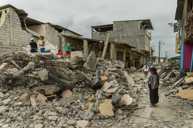 A woman surveys damage in the town of Portoviejo, Ecuador days after a 7.8 magnitude earthquake turned buildings to rubble on Saturday, April 16. The death toll stands at 570 and is expected to keep climbing. More than 7,000 were injured.
