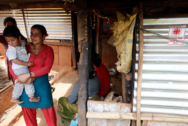 Madre e hijo frente al albergue de lámina construido por Caritas en Kantitar, en el distrito de Kavrepalanchowk, 45 Km. al este de Katmandú (abril de 2016). Foto por Matthieu Alexandre/Caritas
