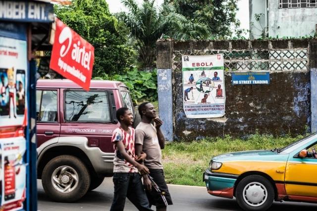 Personas pasando por el frente de un cartel sobre el ébola en Savage Street. Fotografía: Tommy Trenchard/Caritas