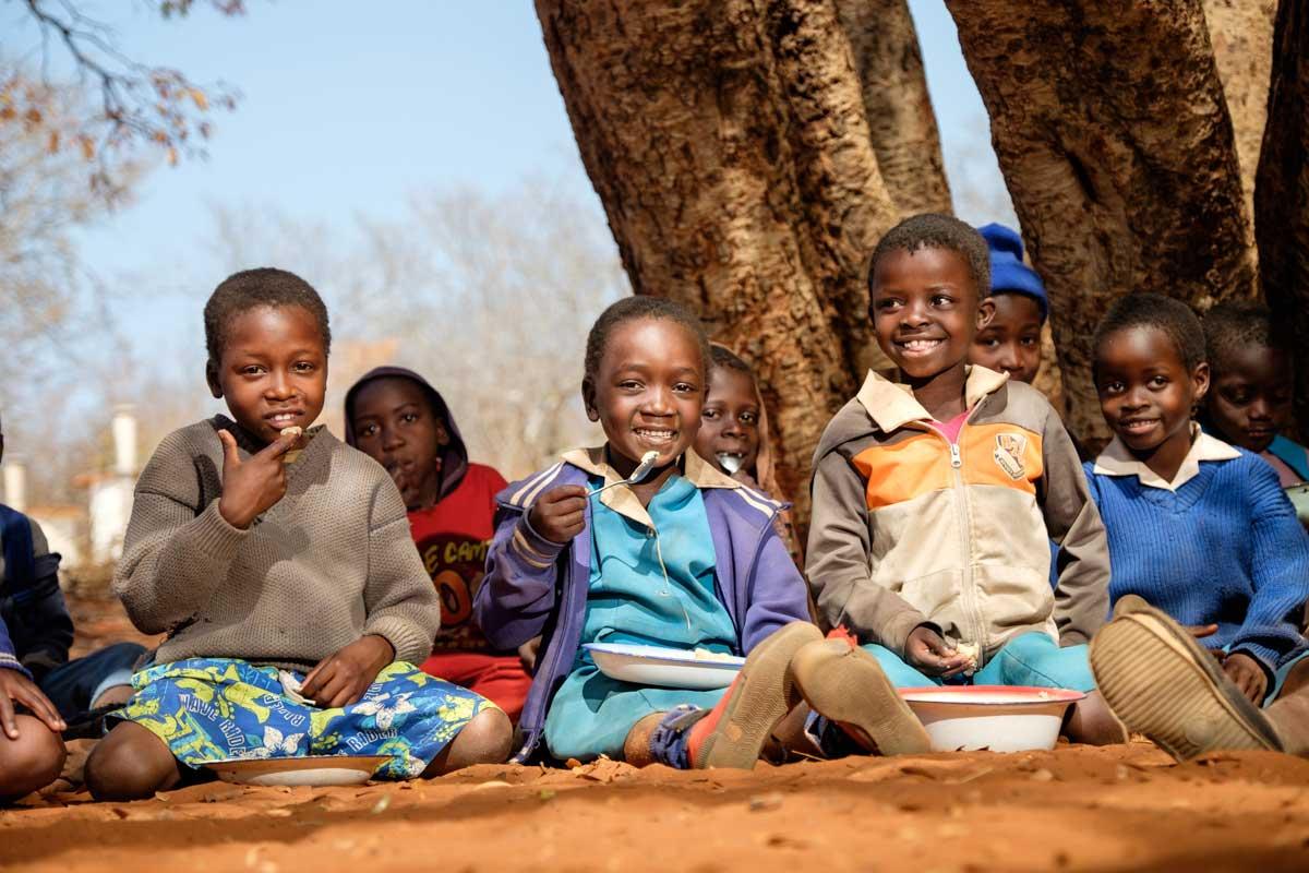 Brillant (7 años) a la izquierda, Cute (6 años) en el centro, Thoselihle (6 años) comen su porción de crema de maiz.