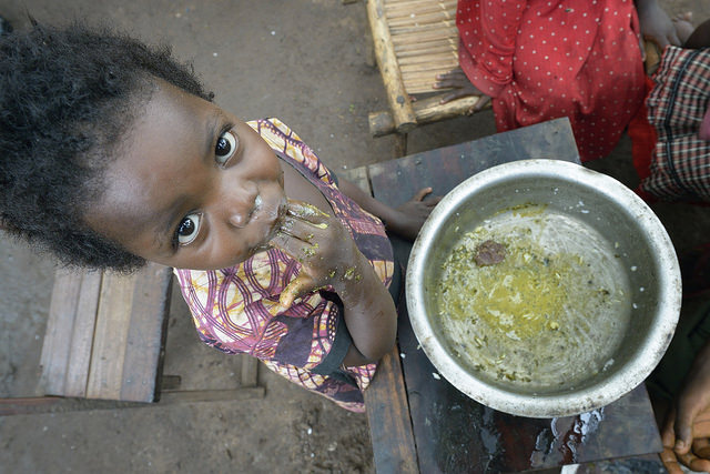 Two-year old Jennifer Angel enjoys the last of her family's meal in a camp for for than 5,000 displaced people in Riimenze, in South Sudan's Gbudwe State, what was formerly Western Equatoria. Photo by Paul Jeffrey/Caritas