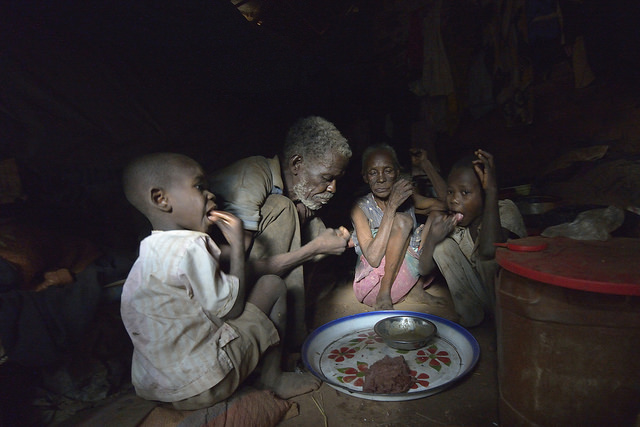 A family shares a meal inside their shelter in a camp