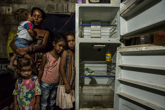 "Leidy Cordova, a 37-year-old mother, poses for a portrait with her four children. The entire family went the entire day without eating. Inside their home, a broken refrigerator was empty except for half a bag of corn flour and a bottle of vinegar. ""My kids tell me they're hungry,"" said Ms. Cordova as her family looked on. ""And I all can say to them is to grin and bear it."" Photo by Caritas"