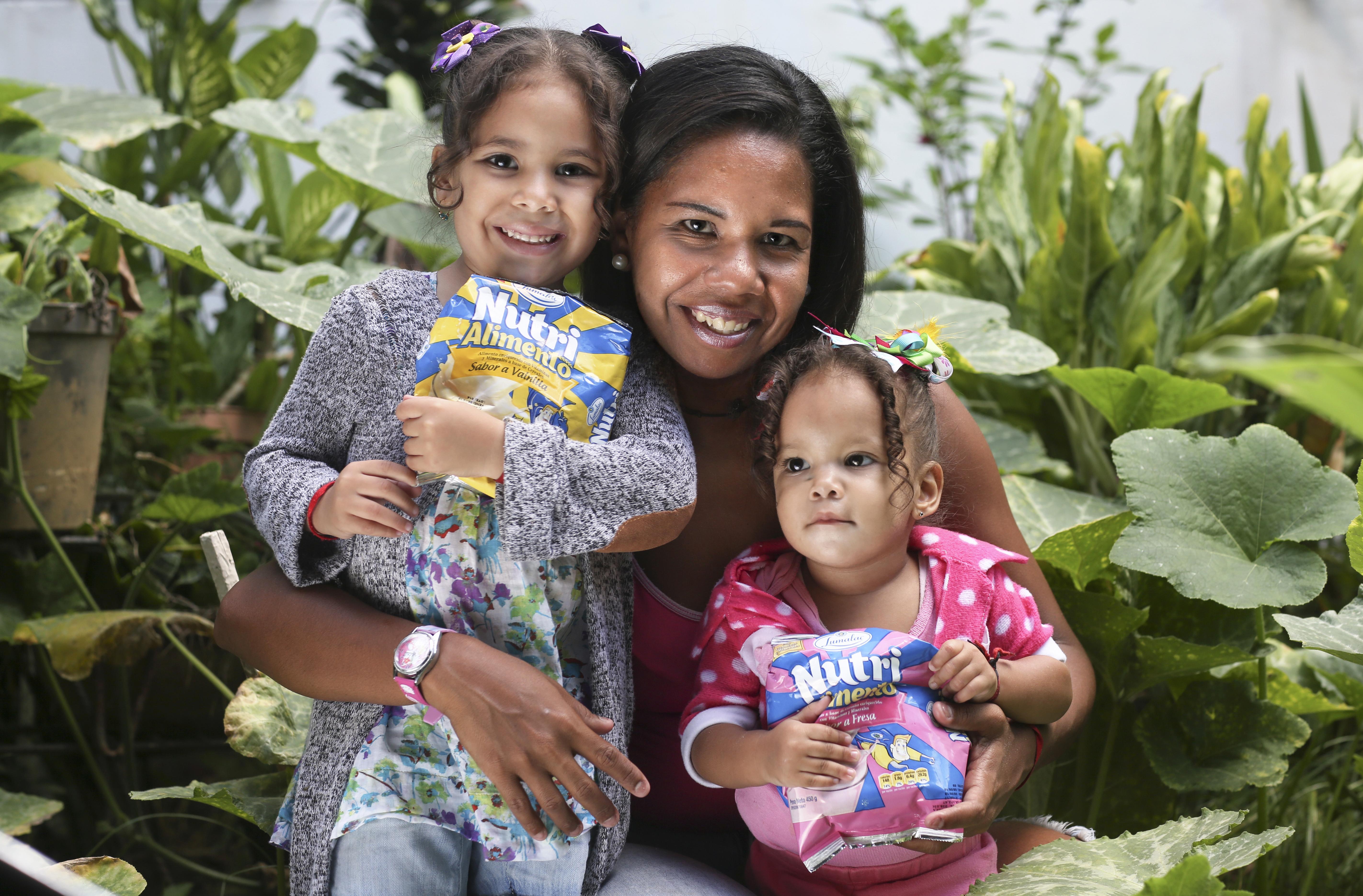 Milena Sosa, 34, with her daughters Barbara, 4, and Estefany 22 months, with their nutritional supplements given to them by Caritas Venezuela volunteers.