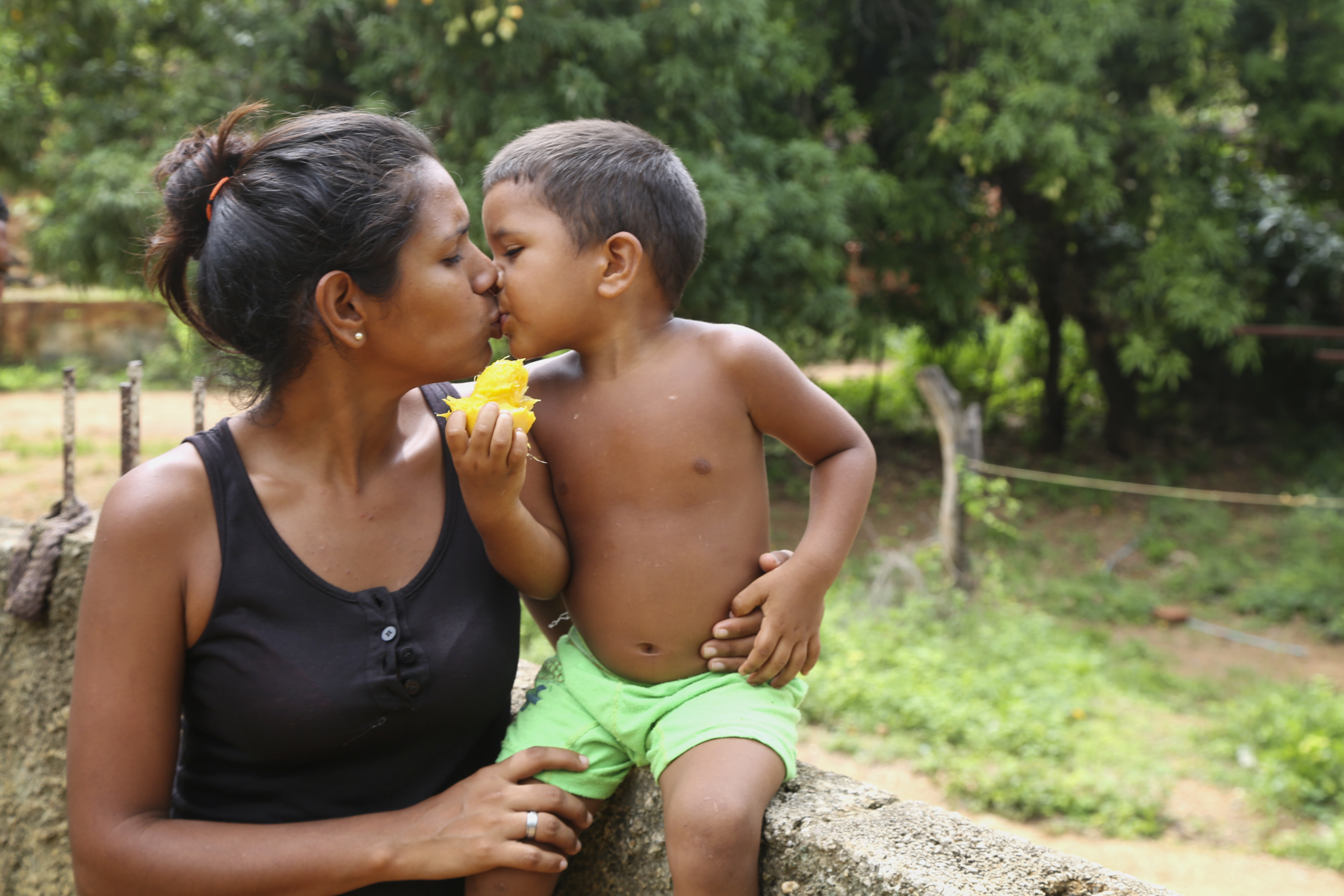 Yusmarelis Acu–a, 29, gets a kiss from her son Greivis, 3, outside their home in Venezuela.