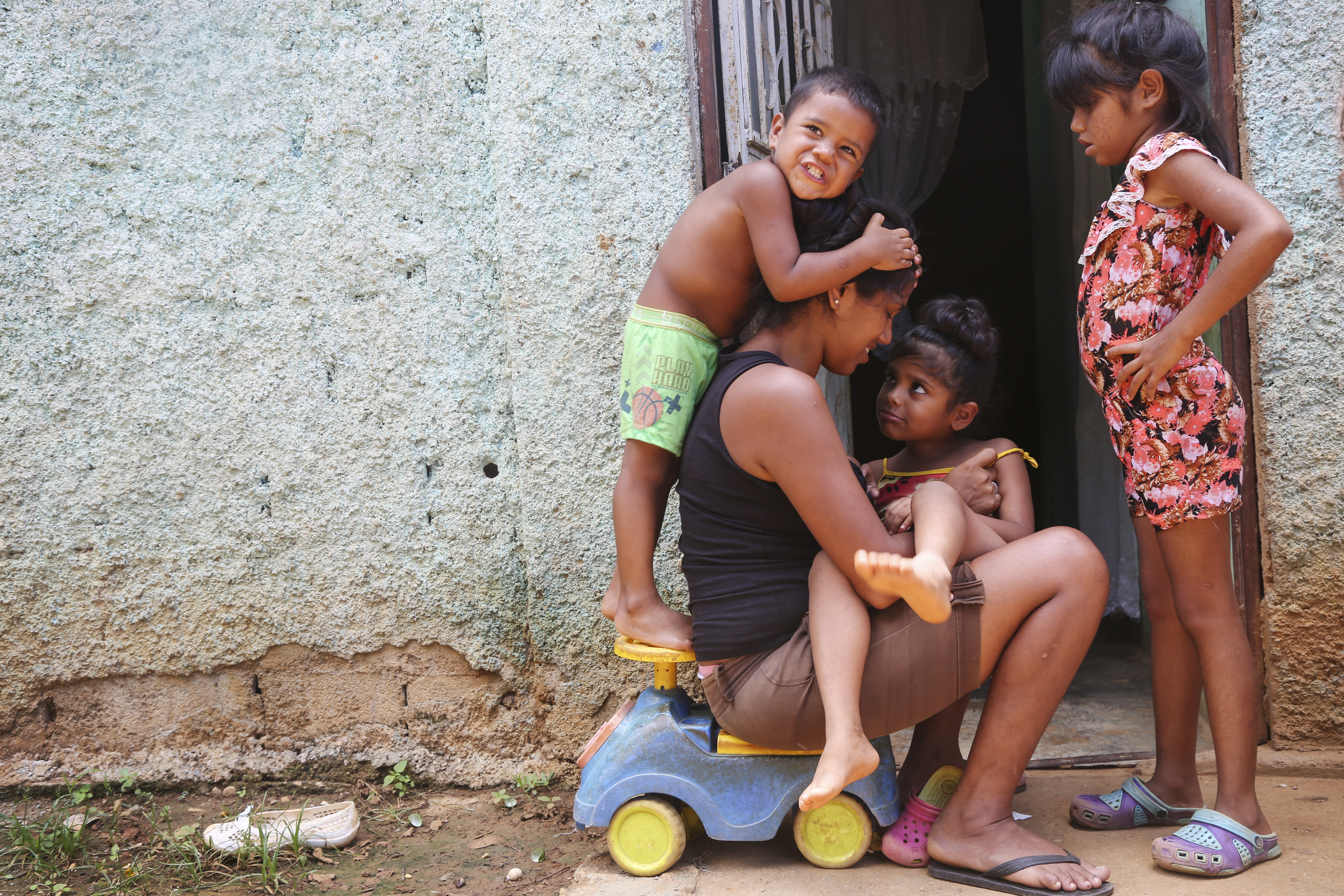 Yusmarelis Acuña, 29, snuggles with her daughter, Grendimar, 6, while her son Greivis, 3, climbs on her and eldest daughter, Valentina,7, chats with her outside their home in Tomuso, Venezuela.