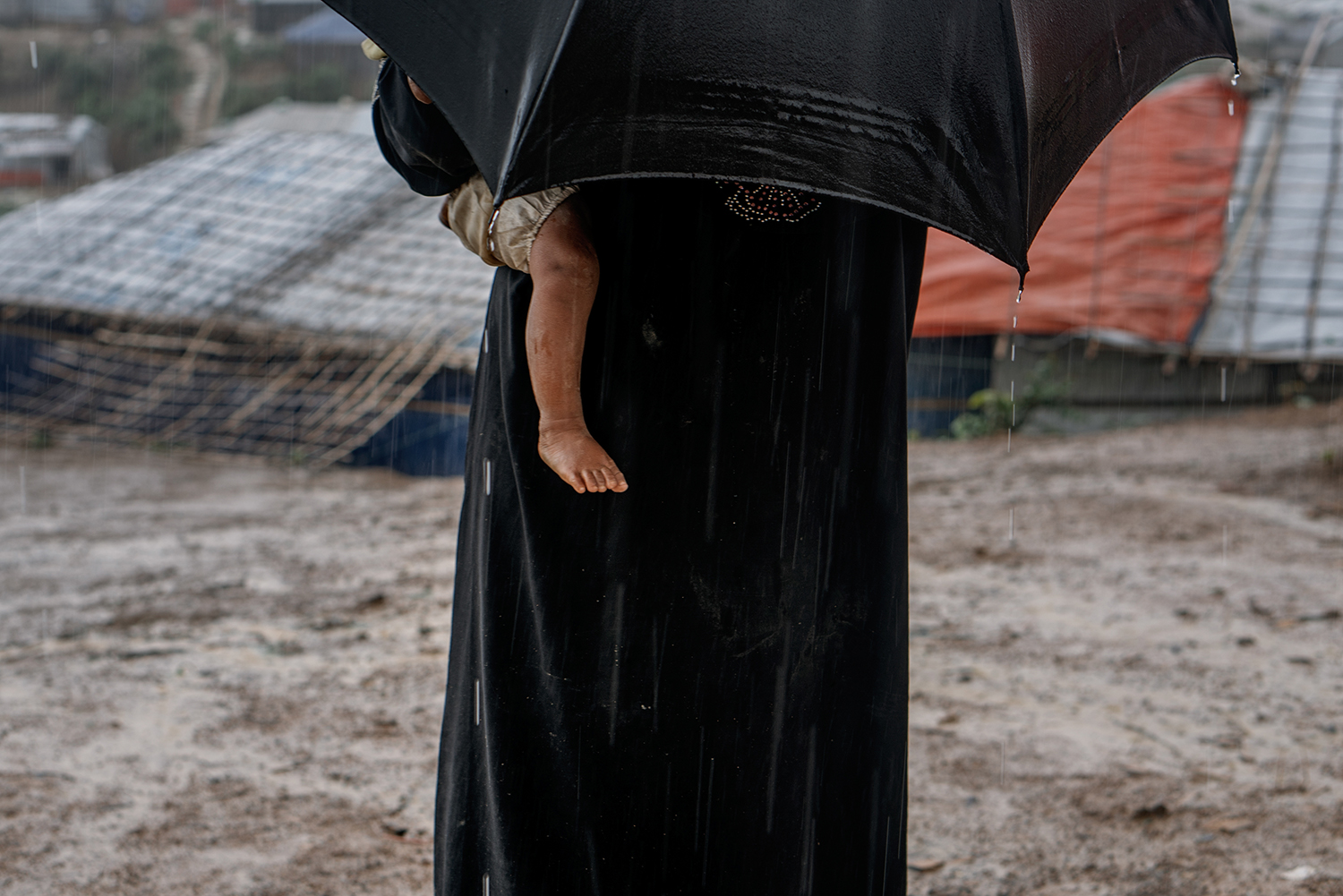 Mother and child in the rain at the Rohingya refugee camp.