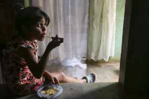 Valentina, 7, eats a bowl of rice with bits of ground meat at her home in Tomuso, Venezuela.