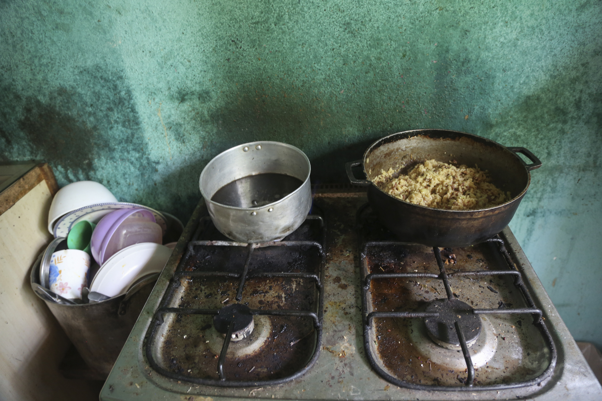 Lunch for six children and three adults cooks on Yusmarely's mother's stove. The ingredients in the two pots are almost equivalent to what the average Venezuelan earns in a month.