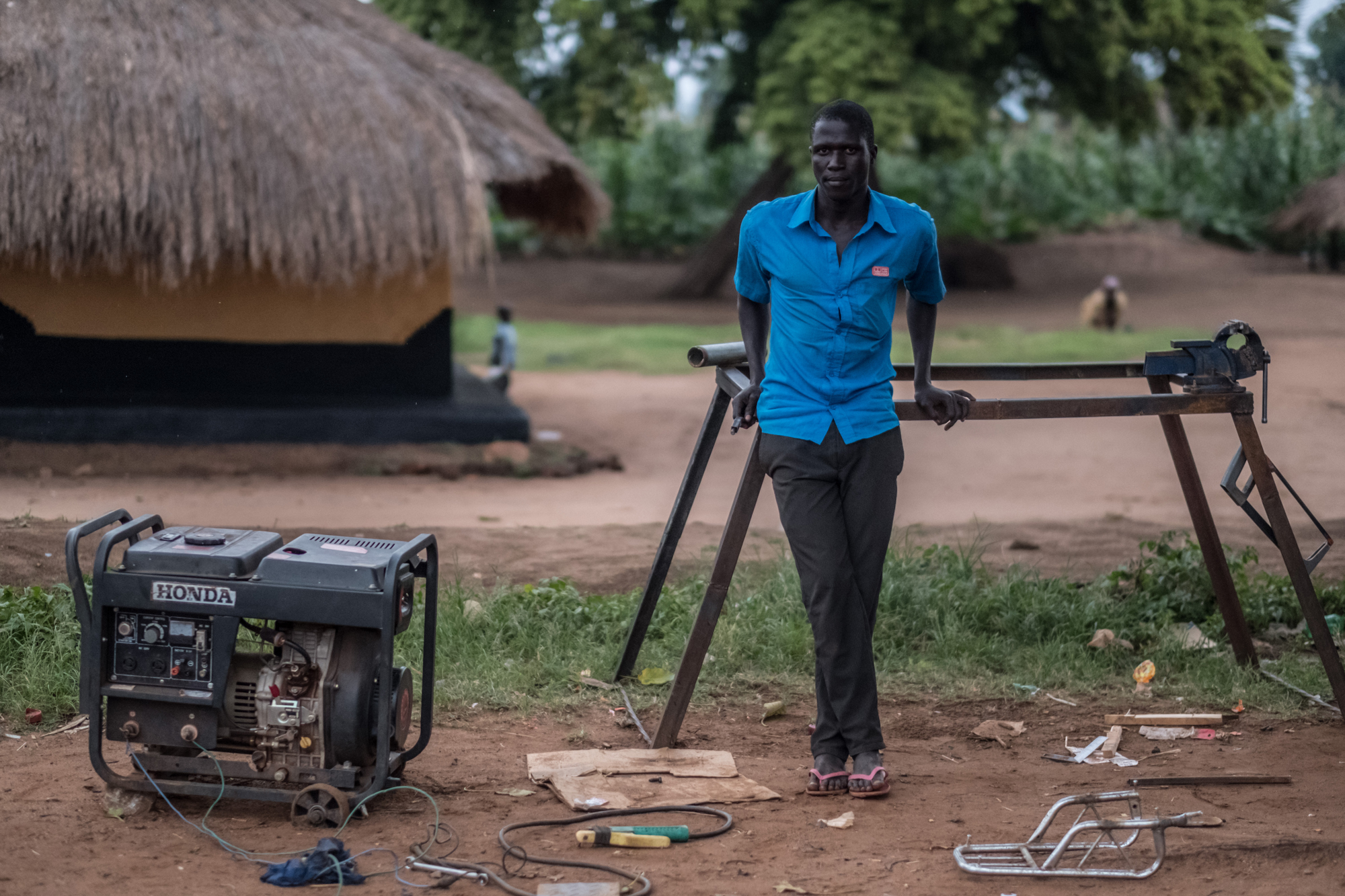 A young man working on a generator in Uganda.