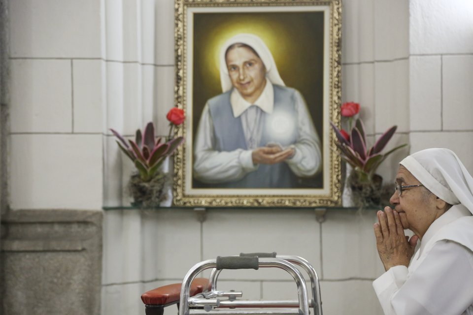 In Venezuela, a sister prays in the chapel in front of a portrait of their congregation's founder, Sister Carmen Rendiles, who was recently beatified by Pope Francis.
