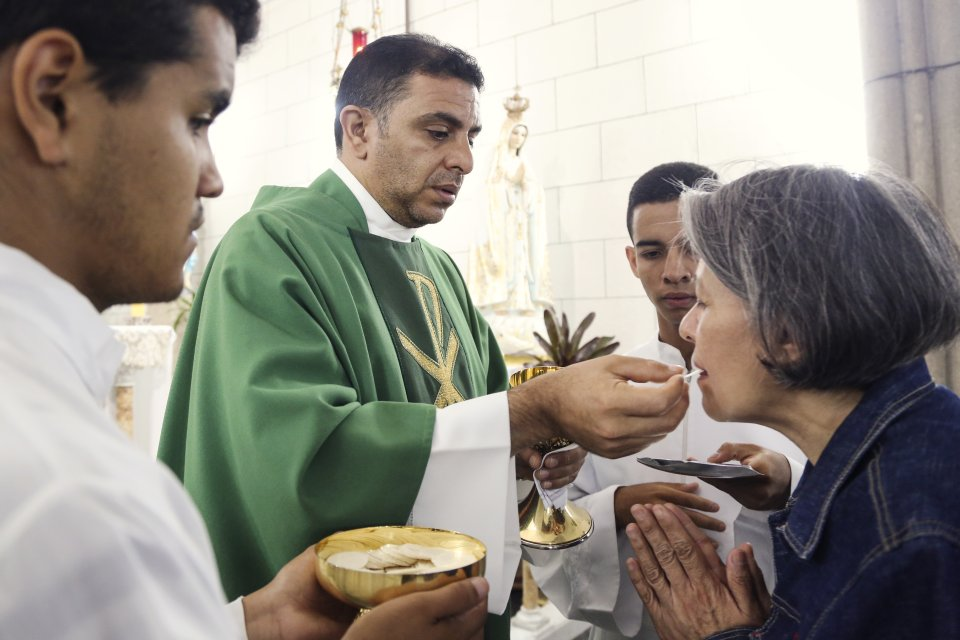 Fr. Emiliio Matos gives communion to parishioners at the Las Siervas de Jesœs de Venezuela Congregation in Caracas.