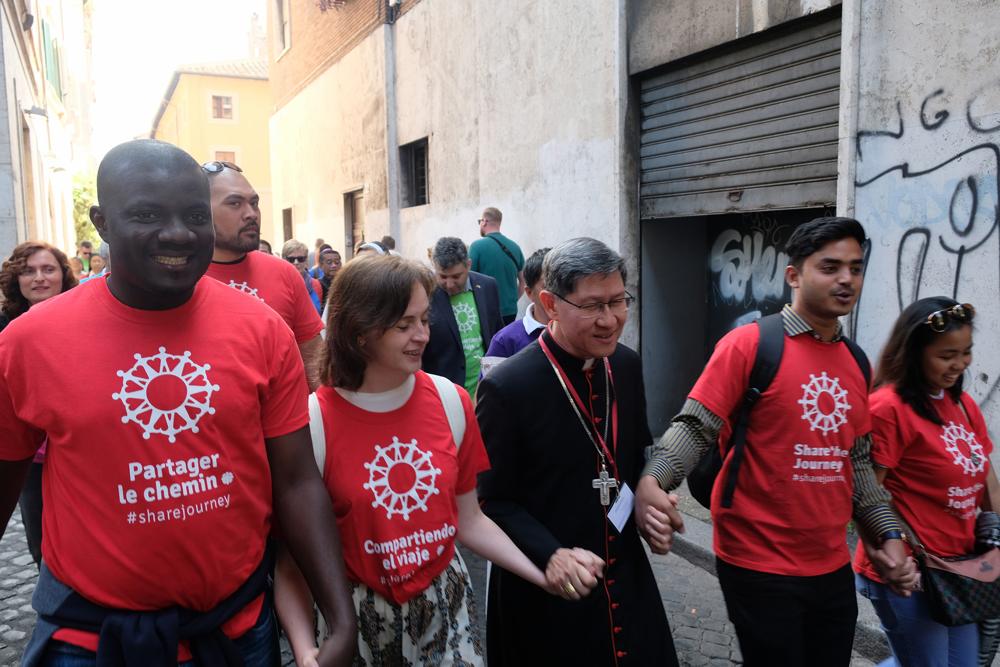 El Cardenal Tagle caminando junto a un grupo de migrantes en Roma