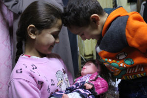 Two of Maram's children play with a doll in their tiny elevator room apartment in Syria