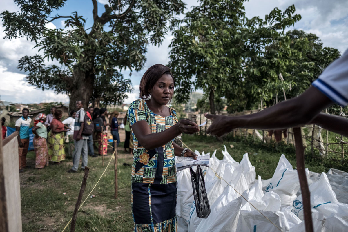 Kahindo Alima, 34, who comes from a neighbourhood affected by Ebola, collects food from Caritas at a distribution centre in Beni, DRC.