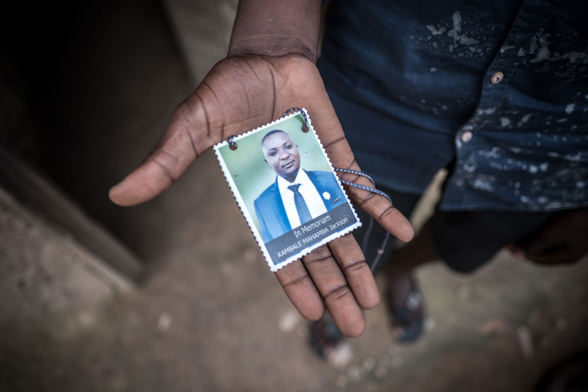 Kambale Kamatosha Serge, 20, holds a photograph of his brother, Jackson, who lost his life to the ebola epidemic in April 2019.