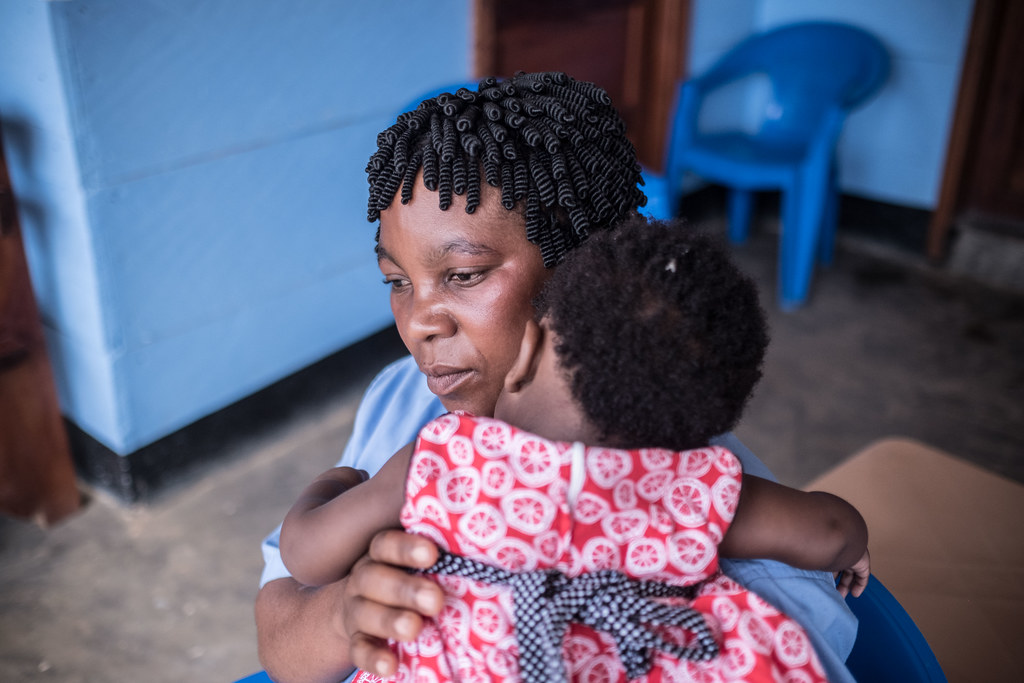 Ebola survivor Kahambo Kiavero Fazero, 38, looks after the child of an Ebola patient at a Caritas-supported nursery in Mangina, DRC.