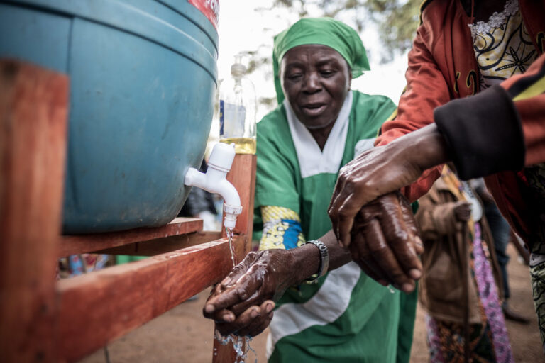Churchgoers wash their hands using a bucket provided by Caritas after a morning mass in Butembo, DRC.